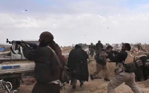 Video released by Isil from inside Baghouz shows fighters firing their weapons during clashes with the SDF - Credit: Amaq Agency