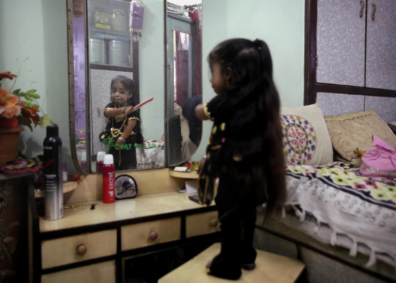 Indian Jyoti Amge, 18, who stands at 61.95 centimeters (2 feet), combs her hair in front of a mirror as she prepares for a press conference with Guinness World Records in Nagpur, India, Friday, Dec. 16, 2011. Officials from Guinness were expected to measure Amge later Friday and declare her the World's Shortest Woman. (AP Photo/Manish Swarup)