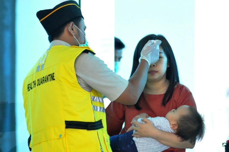 An Indonesian health official checks the temperature of passengers at the airport in Palu, Central Sulawesi. Indonesia has not reported any confirmed infections so far