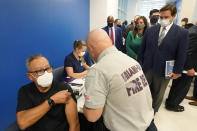 FILE - In this Jan. 4, 2021, file photo, Florida Gov. Ron DeSantis, right rear, watches as Carlos Dennis, left, 65, rolls up his sleeve so that Miami-Dade County Fire Rescue paramedic, Capt. Javier Crespo, can administer a COVID-19 vaccine shot at Jackson Memorial Hospital in Miami. With frustration rising over the slow rollout of the vaccine, state leaders and other politicians are turning up the pressure, improvising and seeking to bend the rules to get shots in arms more quickly. (AP Photo/Wilfredo Lee, File)