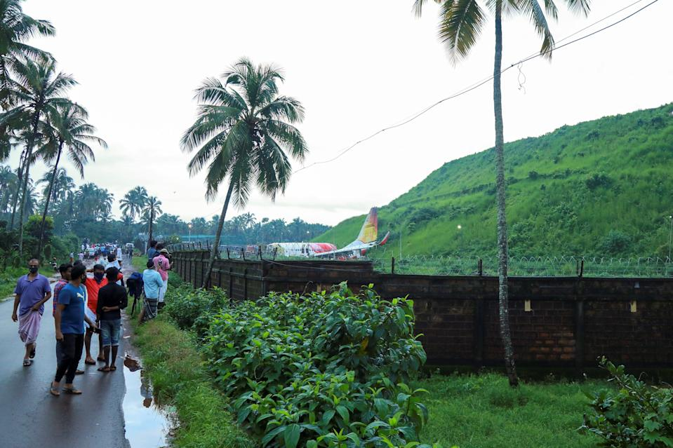 People gather near the wreckage of an Air India Express jet at Calicut International Airport in Karipur, Kerala, on August 8, 2020. - Fierce rain and winds lashed a plane carrying 190 people before it crash-landed and tore in two at an airport in southern India, killing at least 18 people and injuring scores more, officials said on August 8. (Photo by Arunchandra BOSE / AFP) (Photo by ARUNCHANDRA BOSE/AFP via Getty Images)