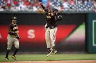 San Diego Padres' Fernando Tatis Jr., right front, celebrates with Trent Grisham, obscured, and Tommy Pham, left, after the continuation of a suspended baseball game against the Washington Nationals, Sunday, July 18, 2021, in Washington. The Padres won 10-4. (AP Photo/Nick Wass)