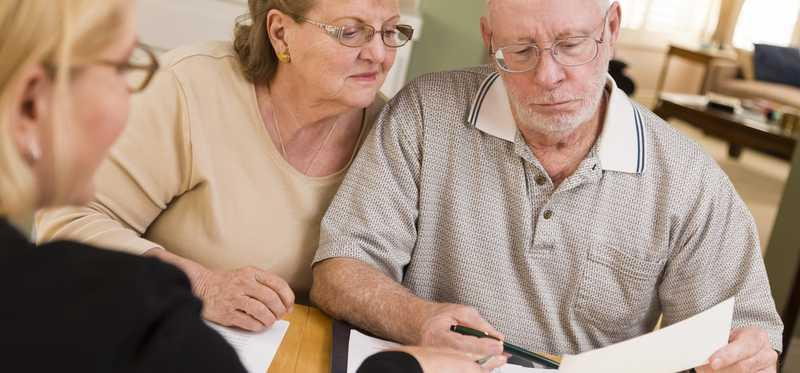 An elderly couple looks at paperwork and talks with an advisor.