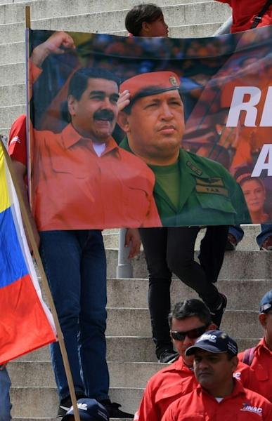 People hold a banner with images of Venezuelan President Nicolas Maduro (L) and late president Hugo Chavez during a pro-government demonstration in Caracas