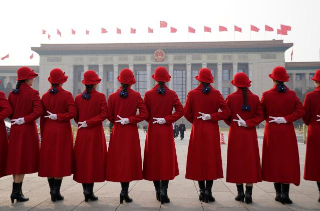 <p>Hotel ushers pose for a photo at Tiananmen Square as delegates attend the second plenary session of the National People's Congress (NPC) in Beijing on March 9, 2018. (Photo: Jason Lee/Reuters) </p>