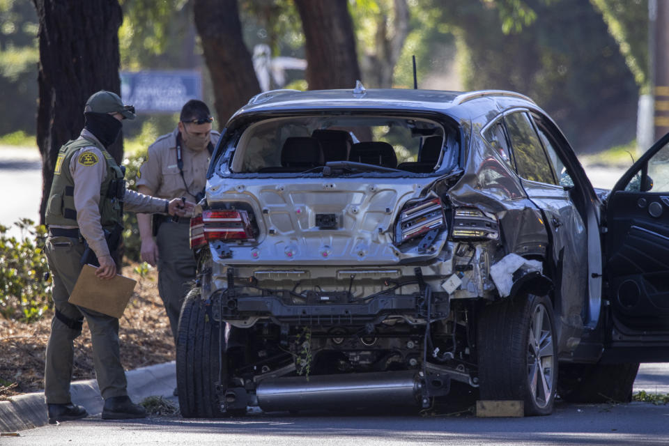 Los Angeles County Sheriff deputies gather evidence from the car that golf legend Tiger Woods was driving when seriously injured in a rollover accident on February 23, 2021 in Rolling Hills Estates, California.