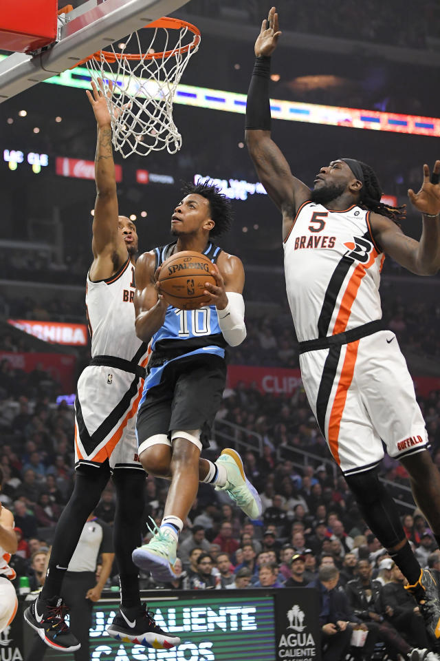 Cleveland Cavaliers guard Darius Garland, center, goes up for a shot as Los Angeles Clippers guard Rodney McGruder, left, and forward Montrezl Harrell defend during the first half of an NBA basketball game Tuesday, Jan. 14, 2020, in Los Angeles. (AP Photo/Mark J. Terrill)