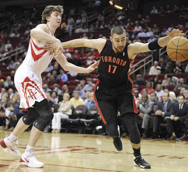 Toronto Raptors' Jonas Valanciunas (17) goes after a loose ball under pressure from Houston Rockets' Omer Asik (3) in the first half of an NBA basketball game Monday, Nov. 11, 2013, in Houston. (AP Photo/Pat Sullivan)