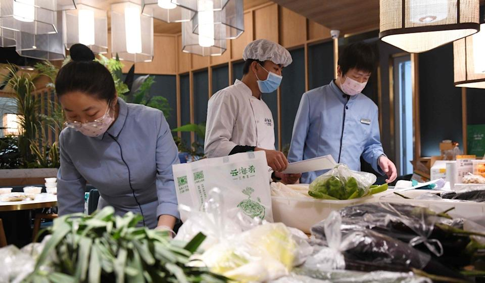 Workers at Yunhaiyao restaurant are seen packing vegetables before delivering them to residents in a nearby residential compound in Tongzhou, east of Beijing, on February 18. Photo: Agence France-Presse