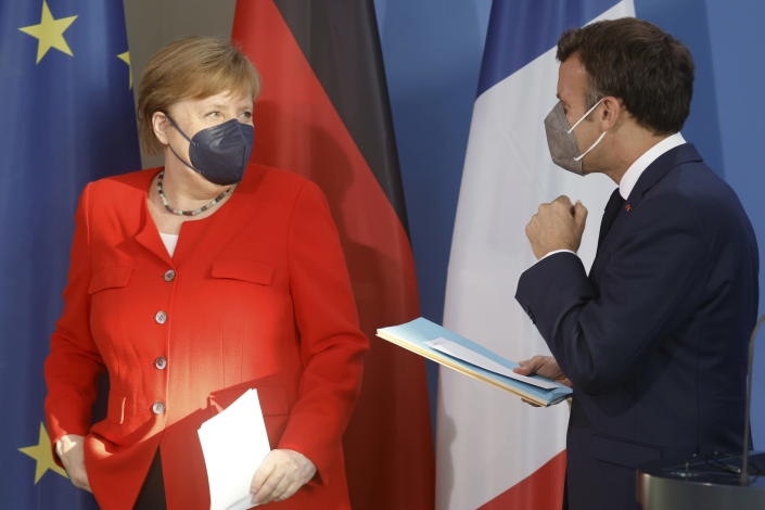 German Chancellor Angela Merkel, left, and French President Emmanuel Macron prepare to give a joint statement to journalists, at the chancellery in Berlin, Germany, Friday June 18, 2021. (Axel Schmidt/Pool via AP)