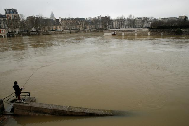 <p>A man fishes on the flooded banks of the River Seine in Paris, France, after days of almost non-stop rain caused flooding in the country, Jan. 27, 2018. (Photo: Pascal Rossignol/Reuters) </p>
