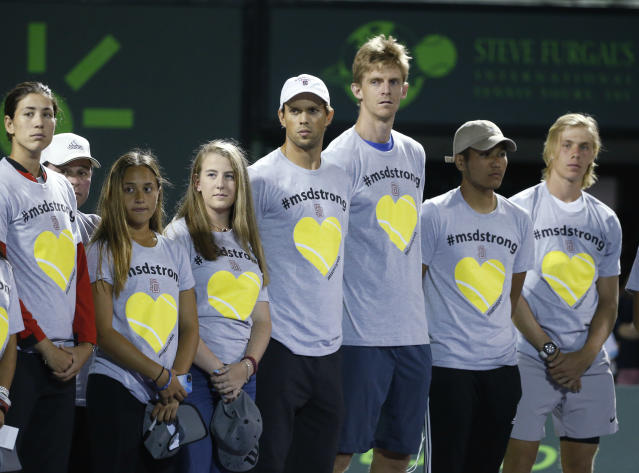 Players Mike Bryan, center left, and Kevin Anderson, center right, stand with members of the Marjory Stoneman Douglas High School tennis team during a ceremony honoring the victims of the school shooting in February, before the start of the night session of the Miami Open, Saturday, March 24, 2018, in Key Biscayne, Fla. (AP Photo/Wilfredo Lee)