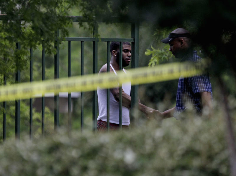 A man, at left, is greeted by an investigator inside a housing complex at the scene of a shooting, Sunday, June 10, 2012, in Auburn, Ala. Auburn Police Chief Tommy Dawson said authorities responded during the night to a report of multiple gunshot victims at the apartment complex, but he released no immediate information as the building dawned Sunday cordoned in yellow tape. (AP Photo/David Goldman)