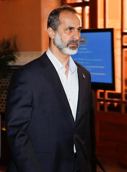 "Moaz al-Khatib, head of a new coalition of Syrian opposition groups arrives at a meeting of the Friends of the Syrian People in Marrakech, Morocco, Wednesday Dec. 12, 2012. The Syrian opposition called for ""real support"" and not just recognition on Wednesday, hours after the U.S. declared its new coalition was the ""legitimate representative"" of its country's people. Bnner behind reads: 4th meeting of the group of ""Friends of the Syrian People"". (AP Photo/Abdeljalil Bounhar)"