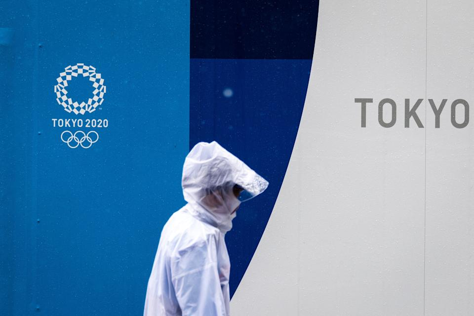 A pedestrian walks past a Tokyo 2020 Olympic and Paralympic Games logo in Tokyo