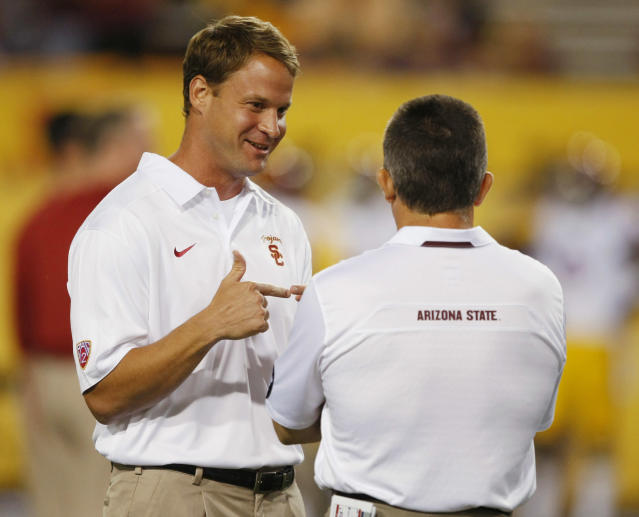 "FILE - Southern California coach Lane Kiffin talks to Arizona State coach Todd Graham before an NCAA college football game in a Saturday, Sept. 28 2013, file photo, in Tempe, Ariz. USC has fired football coach Lane Kiffin, the Trojans announced early Sunday, Sept. 29, 2013. Athletic director Pat Haden said in a short news release that he informed Kiffin of the decision ""upon the team charter's arrival back in Los Angeles early Sunday morning following USC's 62-41 loss at Arizona State."" (AP Photo/Rick Scuteri, File)"