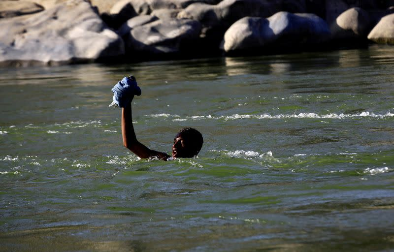 FILE PHOTO: An Ethiopian fleeing the ongoing fighting in Tigray region, lifts his clothes as he crosses the Setit river on the Sudan-Ethiopia border in Hamdayet village in eastern Kassala state