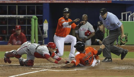 Miami Marlins player Jose Reyes and home plate umpire Dale Scott watch as Philadelphia Phillies catcher Carlos Ruiz (51) tags Marlins runner Giancario Stanton (27) out at home during the fourth inning of a MLB baseball game in Miami, Sunday, Sept. 30, 2012. (AP Photo/J Pat Carter)