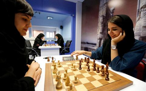 Iranian chess players Mitra Hejazipour (L) and Sara Khademalsharieh play at the Chess Federation in the capital Tehran on October 10, 2016. - Credit: AFP
