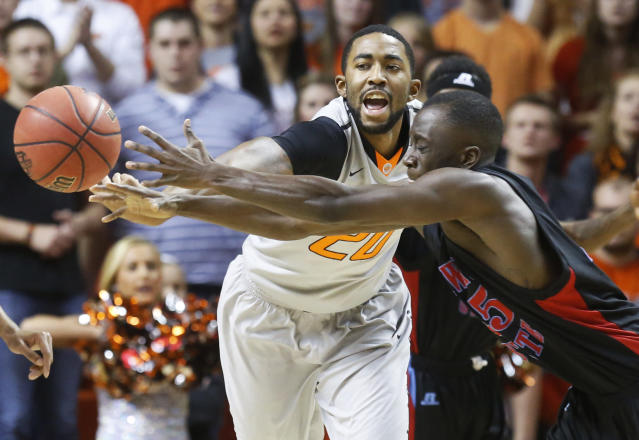 Oklahoma State's Michael Cobbins, left, and Delaware State's Ashwell Boyd, right, reach for a loose ball in the first half of an NCAA college basketball game in Stillwater, Okla., Tuesday, Dec. 17, 2013. (AP Photo/Sue Ogrocki)