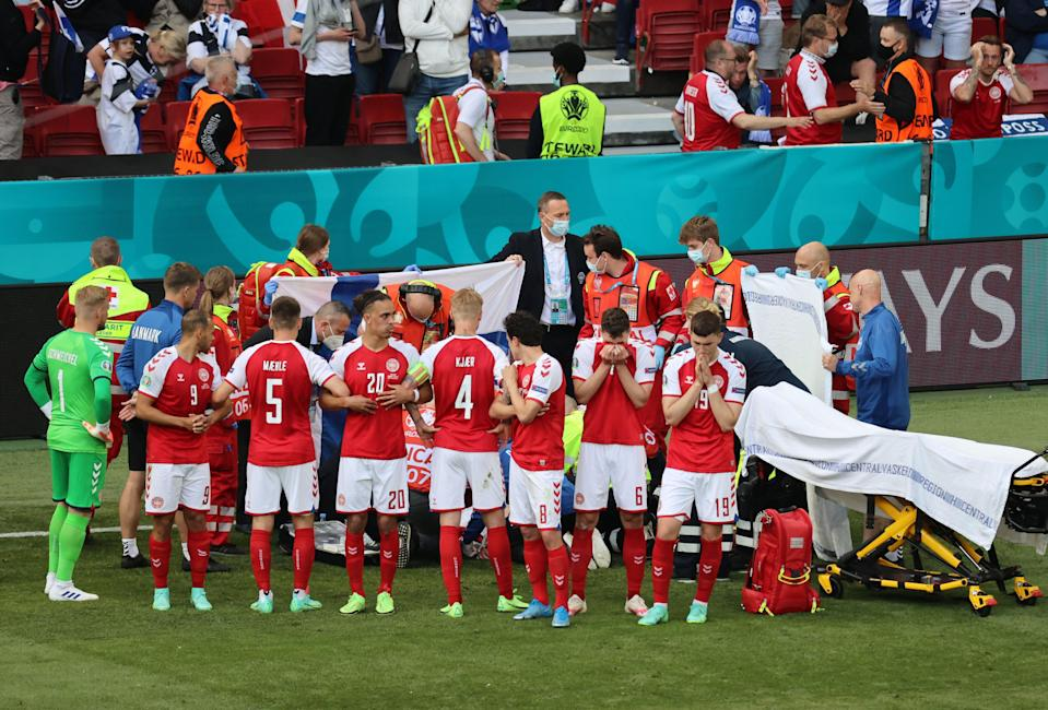 Denmark players shield Christian Eriksen while he receives medical attention (Reuters)