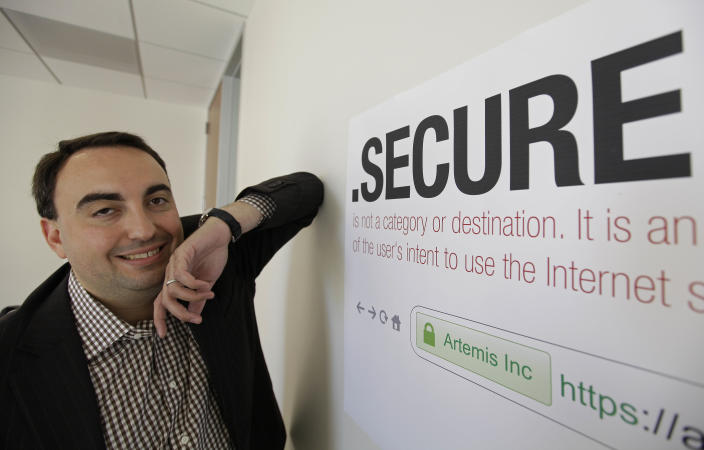 """In this photo taken Friday, June 8, 2012 Alex Stamos CTO of Artemis Internet, an NCC Group Company, poses by a domain name poster at their offices in San Francisco. Some 2,000 proposals have been submitted as part of the largest expansion of the Internet address system since its creation in the 1980s. These suffixes would rival """".com"""" and about 250 others now in use. The organization behind it, the Internet Corporation for Assigned Names and Numbers, will announce a full list and other details in London on Wednesday. (AP Photo/Eric Risberg)"""