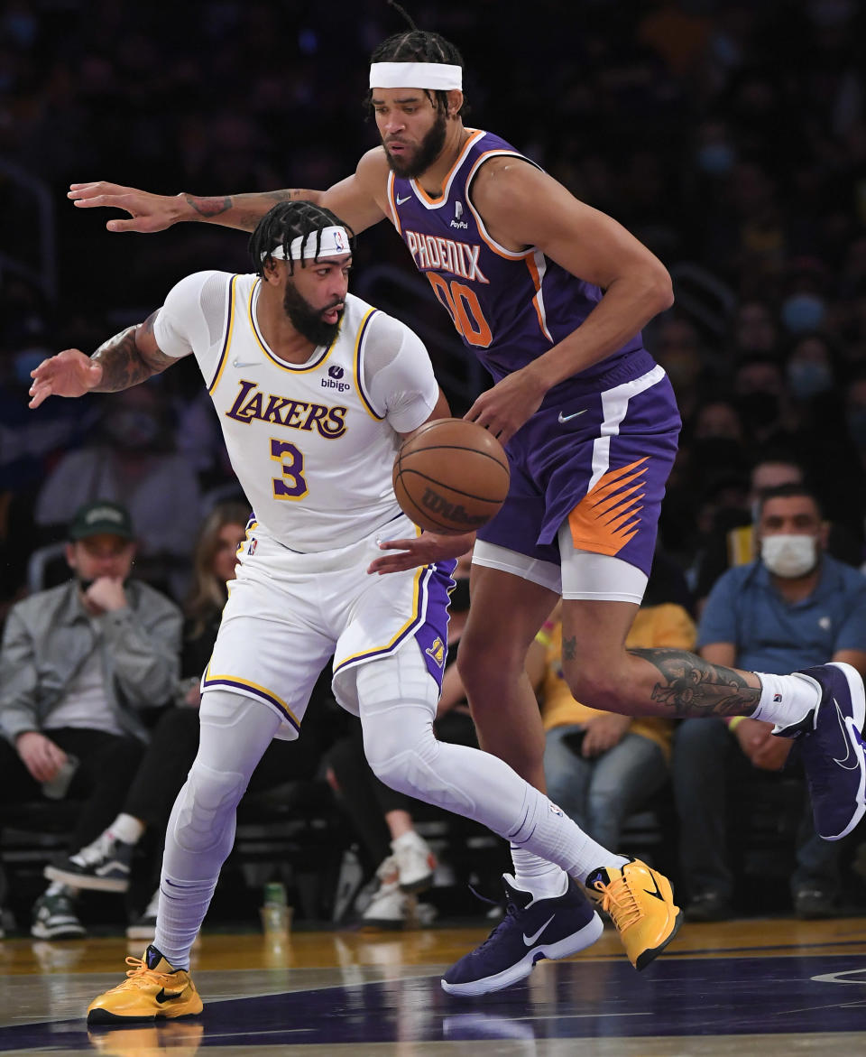 Los Angeles Lakers forward Anthony Davis (3) and Phoenix Suns center JaVale McGee (0) battle for the ball during the first half of a preseason NBA basketball game in Los Angeles, Sunday, Oct. 10, 2021. (AP Photo/John McCoy)