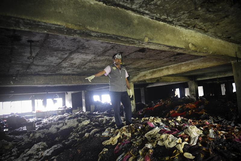 An investigator surveys the scene of a fire at a garment factory in Dhaka, Bangladesh, Thursday, May 9, 2013. A fire in an 11-story garment factory in Bangladesh killed eight people, including a ruling-party politician and a top official in the country's powerful clothing manufacturers' trade group, as the death toll from the collapse of another garment factory building passed 900 on Thursday. (AP Photo/Ismail Ferdous)