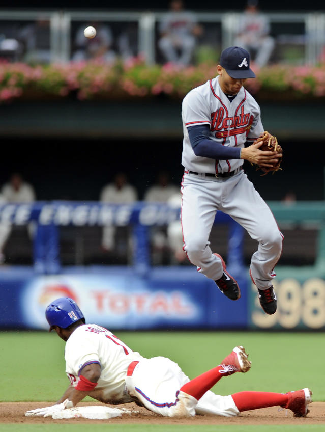 Atlanta Braves' Andrelton Simmons can't handle a wild throw as Philadelphia Phillies' Jimmy Rollins steals second base in the first inning of a baseball game on Saturday, Aug. 3, 2013, in Philadelphia. (AP Photo/Michael Perez)