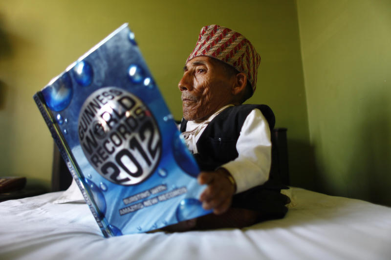 Nepal's Chandra Bahadur Dangi, 72, who says he's only 22 inches (56 centimeters) tall, looks at a copy of the Guinness World Record book at a guesthouse just hours before he was to be measured by officials, in Katmandu, Nepal, Sunday, Feb. 26, 2012. Guinness World Records officials were set to measure Dangi who hopes to be named the world's shortest man Sunday. Dangi is hoping to snatch the title of the world's shortest man from Junrey Balawing of the Philippines, who is 23.5 inches (60 centimeters) tall. (AP Photo/Niranjan Shrestha)