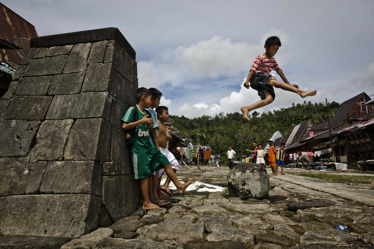 NIAS ISLAND, INDONESIA - FEBRUARY 20:  Children learns to jumping beside the stone tower in Orahili Fau village on February 20, 2013 in Nias Island, Indonesia. Some of historians and archaeologists estimated this is one of remaining Megalithic cultures in existence today. Stone Jumping is a traditional ritual, with locals leaping over large stone towers, which in the past resulted in serious injury and death. Stone jumping in Nias Island was originally a tradition born of the habit of inter tribal fighting on the island of Nias.  (Photo by Ulet Ifansasti/Getty Images)
