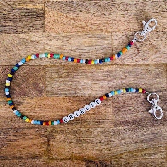 """<p><strong>PeaceLoveAndLuxCo</strong></p><p>etsy.com</p><p><strong>$9.50</strong></p><p><a href=""""https://go.redirectingat.com?id=74968X1596630&url=https%3A%2F%2Fwww.etsy.com%2Flisting%2F828730886%2Fkids-beaded-chain-for-face-mask&sref=https%3A%2F%2Fwww.countryliving.com%2Fshopping%2Fgifts%2Fg33502148%2Fface-mask-accessories%2F"""" rel=""""nofollow noopener"""" target=""""_blank"""" data-ylk=""""slk:Shop Now"""" class=""""link rapid-noclick-resp"""">Shop Now</a></p><p>It might be a bit easier to convince your kid to wear a mask to school if she has a cute personalized chain.</p>"""
