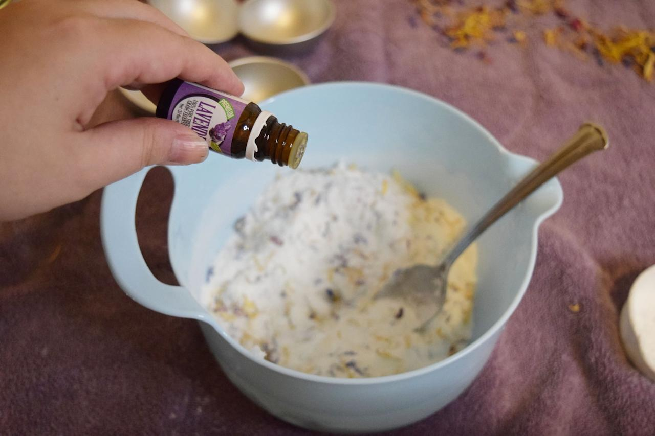 <p>You can use whatever amount of essential oils you want. I added 10 drops of lavender and 10 drops of frankincense to the dry mixture. Once they're mixed in, add the coconut oil and mix again: the mixture should be crumbly. Next, add in the witch hazel a tiny bit at a time. This is the binding agent. You don't want the mixture to become too wet because it'll start to react and expand and basically just go all wrong. Trust me, I made these bath bombs multiple times because I kept doing it wrong. It takes very, very little liquid to get the ingredients to stick together. You want it just wet enough to be able to pack into the molds and hold its shape.</p>