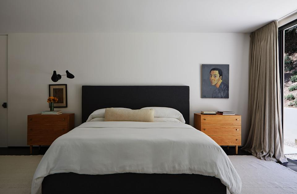 Each side of the custom bed was upholstered in Ralph Lauren cashmere, and the side tables were created with a pair of Milo Baughman chests of drawers from West Coast Modern LA. The white wool kilim rug is from Lawrence of La Brea; the midcentury two-arm sconce is from Stilnovo; and the untitled artwork, a self-portrait, is by Chinese painter Guo Jinyi.