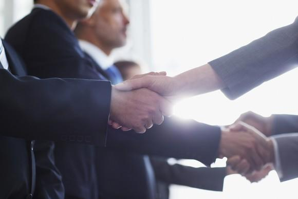 Men in business wear shaking hands
