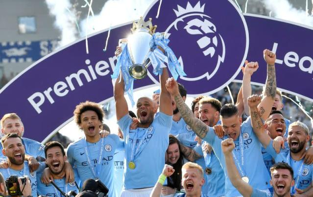 FILE PHOTO: Manchester City skipper Vincent Kompany lifts the trophy as they celebrate defending the Premier League title following a 4-1 victory at Brighton & Hove Albion