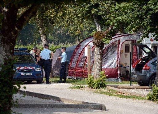 Police talk with investigators near the caravan of the British family killed in the French Alpine village Saint-Jorioz