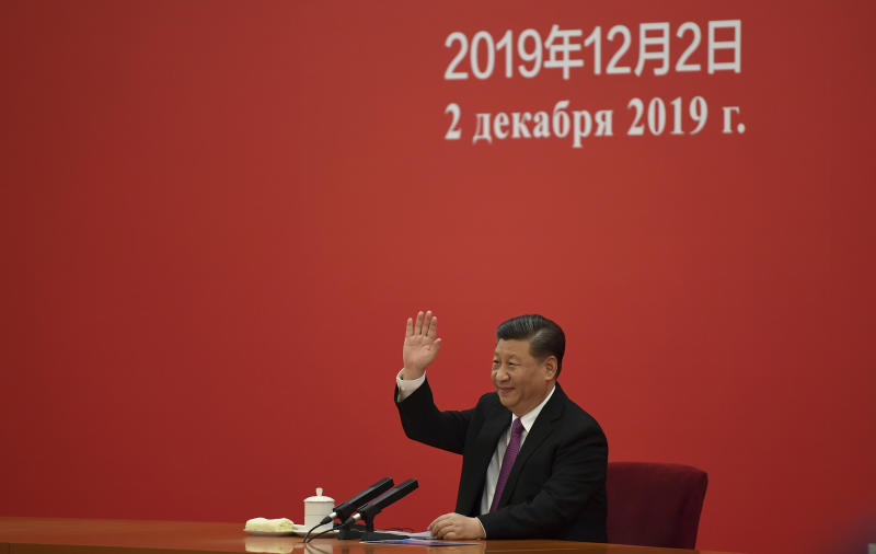 China's President Xi Jinping waves to Russian President Vladimir Putin via a video link from the Great Hall of the People in Beijing, Monday, Dec. 2, 2019. (Noel Celis/Pool Photo via AP)