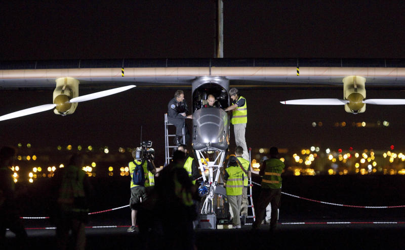 Crew members of an experimental solar-powered airplane check the jumbo jet-size Solar Impulse plane before taking off at Barajas airport in Madrid, Spain, Tuesday, June 5, 2012. The zero fuel airplane arrived in Madrid on May 25, 2012 from Payerne, Switzerland, and now goes on to Rabat, Morocco on its first transcontinental trip. The mission is described as the final dress rehearsal for a round-the-world flight with a new and improved aircraft in 2014. (AP Photo/Alberto Di Lolli)