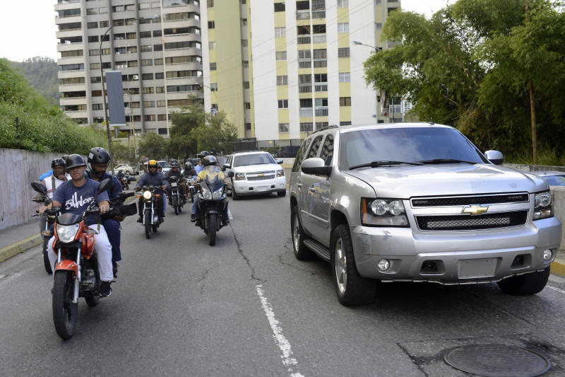 Members of the press ride on motorcycles alongside a caravan of three large vehicles carrying opposition lawmakers, including opposition leader Juan Guaido, to an outdoor theater in El Hatillo after the caravan's vehicles were attacked by government supporters when they attempted to arrive to a session at the National Assembly in downtown Caracas, Venezuela, Wednesday, Jan. 15, 2020. The opposition-controlled National Assembly lawmakers plan to relocate their session at the outdoor theater. (AP Photo/Matias Delacroix)