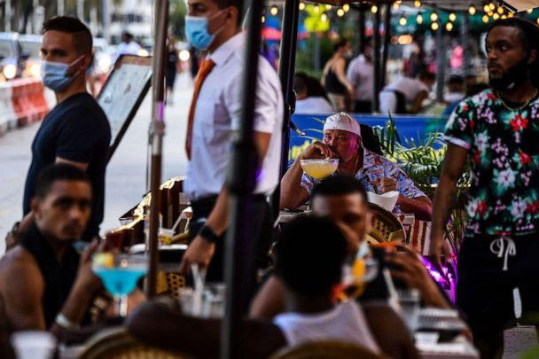 PHOTO: A man enjoys a drink at a restaurant on Ocean Drive in Miami Beach, Fla., July 14, 2020, during the coronavirus pandemic. (Chandan Khanna/AFP via Getty Images)