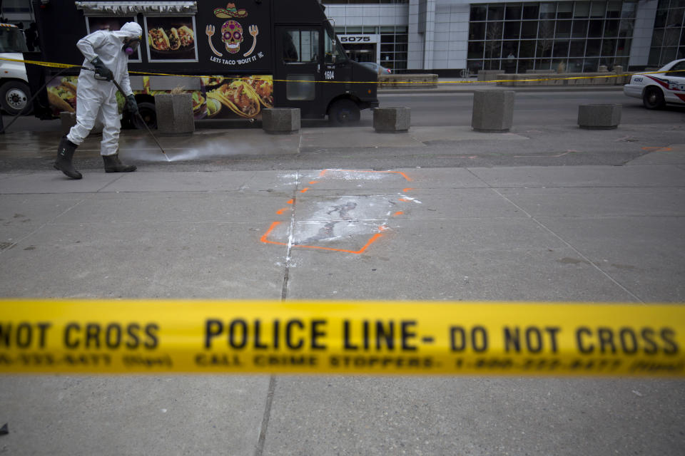 <p>A hazmat worker scrubs the sidewalk of blood and debris near an outline of where a body laid after a mass killing on Yonge St. at Finch Ave. in Toronto. Cole Burston/Getty Images </p>