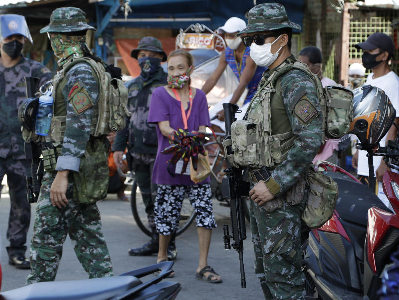 Police officers operate a checkpoint during the start of a lockdown due to a rise in COVID cases in the city of Navotas, Manila, Philippines, Thursday, July 16, 2020. Coronavirus infections continue to rise in the country after reopening the economy that is on the brink of a recession while still struggling to combat the pandemic. (AP Photo/Aaron Favila)