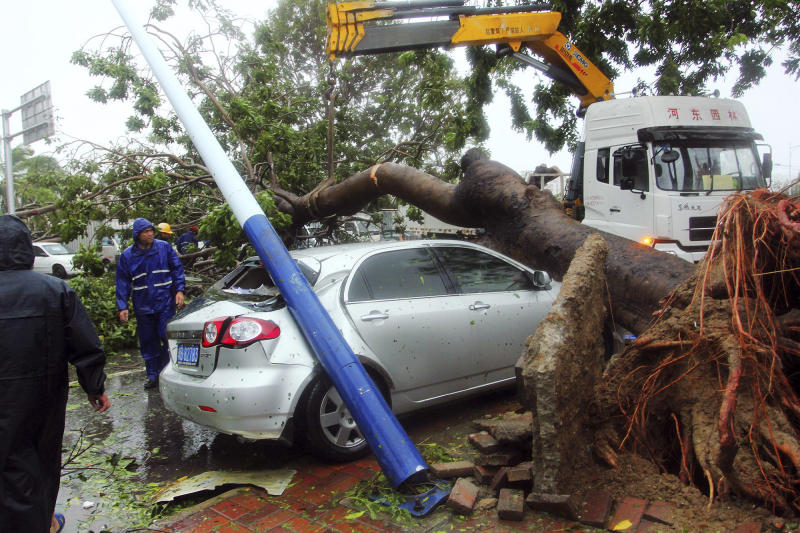 Workers remove a tree that on a car in the aftermath of Typhoon Haiyan after it made landfall in Sanya in south China's Hainan province Sunday Nov. 10, 2013. The deadly Typhoon Haiyan is making its way towards Vietnam and mainland China after devastating parts of Philippines last Friday. (AP Photo) CHINA OUT