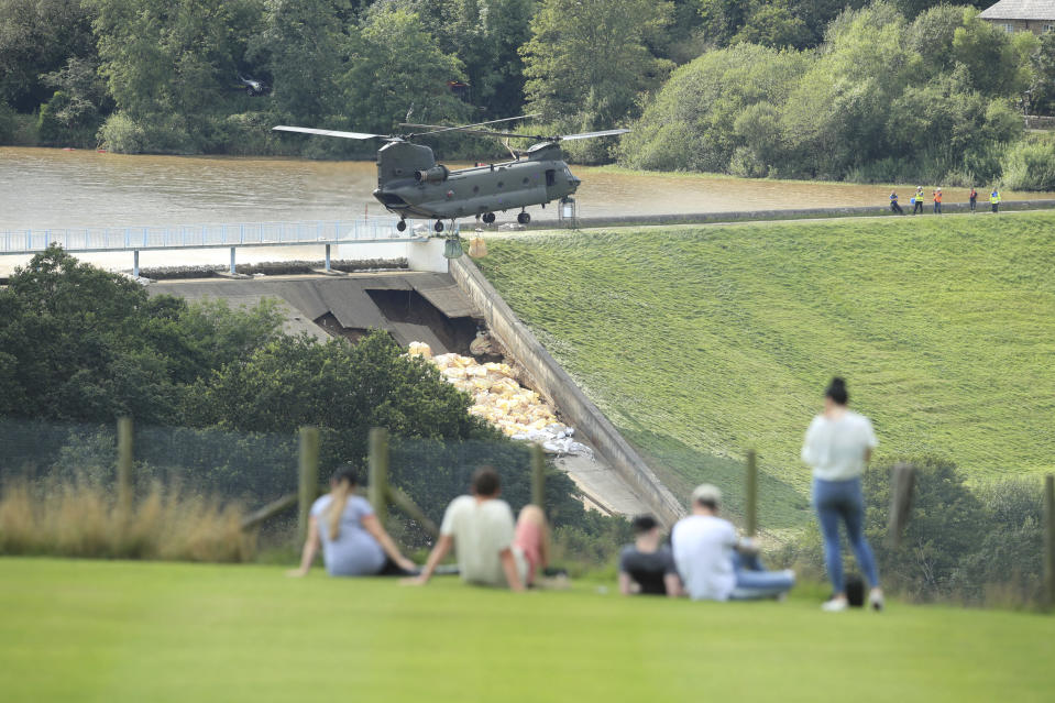 """An RAF Chinook helicopter flies in sandbags to help repair the dam at Toddbrook reservoir near the village of Whaley Bridge in Derbyshire, England, Friday, Aug. 2, 2019. A British military helicopter dropped sandbags Friday to shore up a reservoir wall as emergency services worked frantically to prevent a rain-damaged dam from collapsing. Engineers said they remain """"very concerned"""" about the integrity of the 19th-century Toddbrook Reservoir, which contains around 1.3 million metric tons (1.5 million (U.S tons) of water. (Danny Lawson/PA via AP)"""