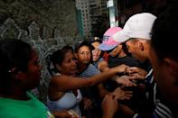 People argue while they queue on the street as they try to buy food outside a supermarket in Caracas, Venezuela March 17, 2017. REUTERS/Carlos Garcia Rawlins