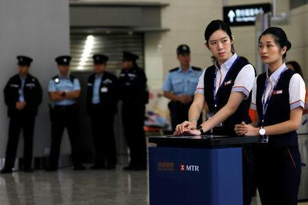 Staff and police stand next to a counter at West Kowloon terminus, during the opening ceremony of the Hong Kong Section of the Guangzhou-Shenzhen-Hong Kong Express Rail Link, in Hong Kong, China September 22, 2018. REUTERS/Tyrone Siu