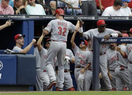 Cincinnati Reds right fielder Jay Bruce (32) is greeted at the dugout after hitting a two-run home run in the third inning of a baseball game against the Atlanta Braves Sunday, July 14, 2013 in Atlanta. (AP Photo/John Bazemore)