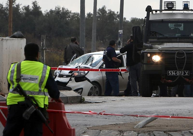 Israeli security forces gather at the scene where a Palestinian man was shot dead after ramming his car into a group of Israelis at Tapuah junction, south of Nablus in the West Bank, on November 8, 2015 (AFP Photo/Jaafar Ashtiyeh)