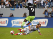 Los Angeles Galaxy forward Jacob Trainor, right, goes after the ball as Seattle Sounders FC forward Obafemi Martins jumps over him during the first half of a Major League Soccer playoff game, Sunday, Nov. 23, 2014, in Carson, Calif. (AP Photo/Mark J. Terrill)